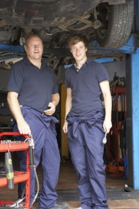 Mechanic and apprentice working on car